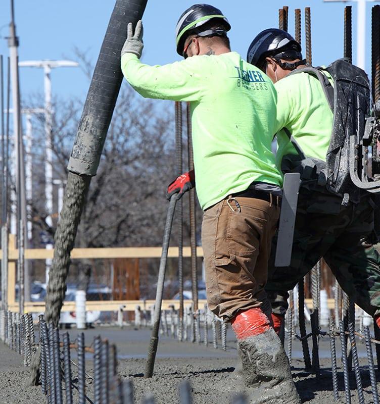 Two concrete construction workers pumping concrete