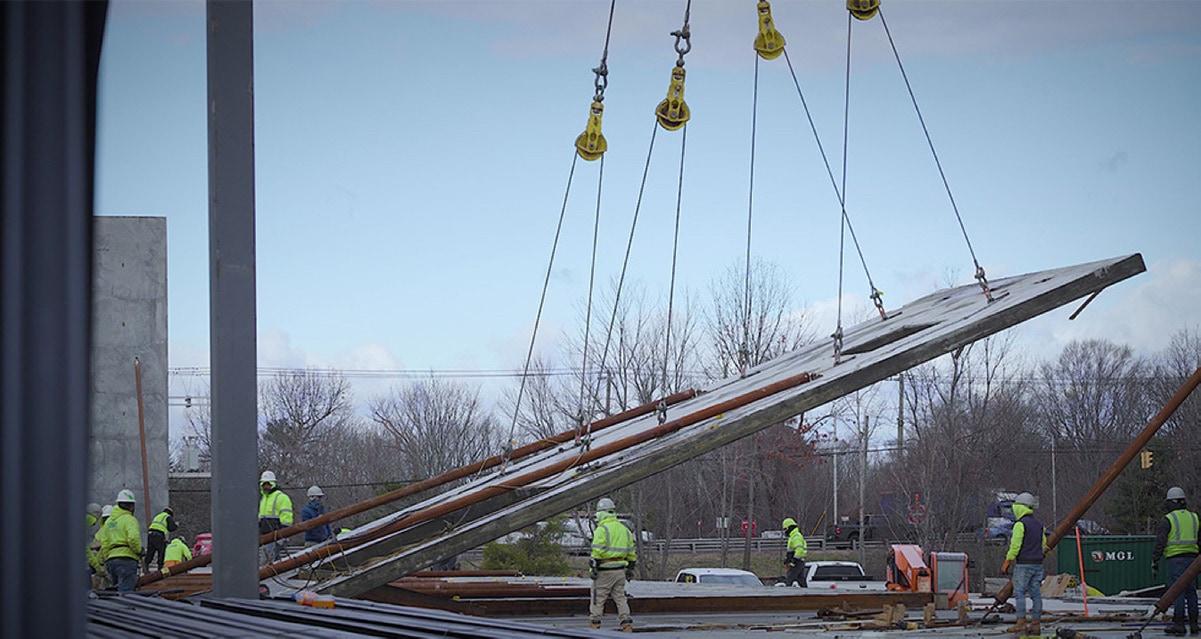 A tilt-wall being erected by a crane