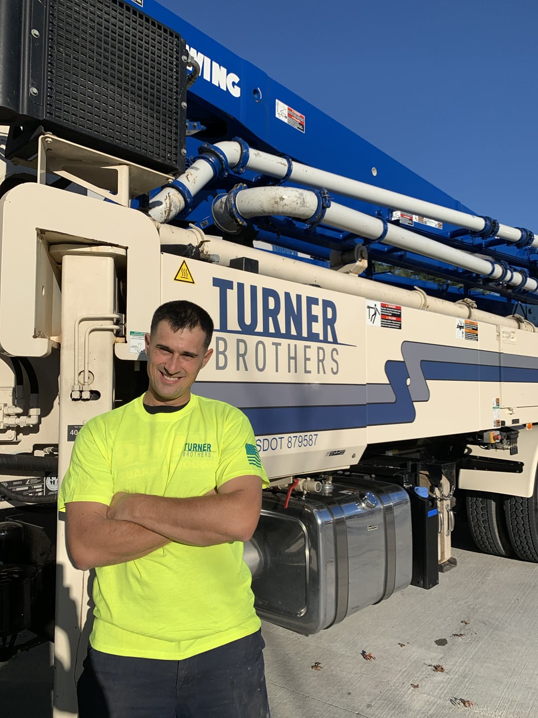 Turner Brothers employee in front of concrete pump truck
